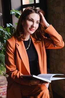 Frau in einer business-terrakotta-jacke sitzt mit einem buch in der hand und glättet ihr haar