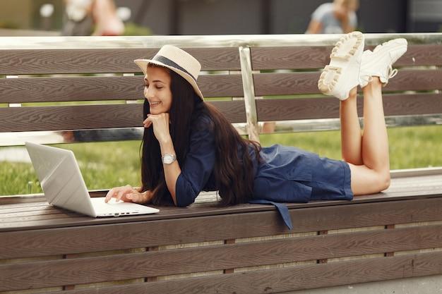 Frau in einer frühlingsstadt. dame mit einem laptop. mädchen sitzt auf einer bank.