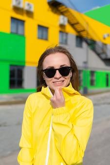Frau in einer gelben jacke und mit sonnenbrille, die mit hellen farbengebäudehintergrund lächelt
