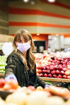 Frau in einer gesichtsmaske mit latexhandschuhen beim einkaufen in einem supermarkt während der coronavirus-quarantäne