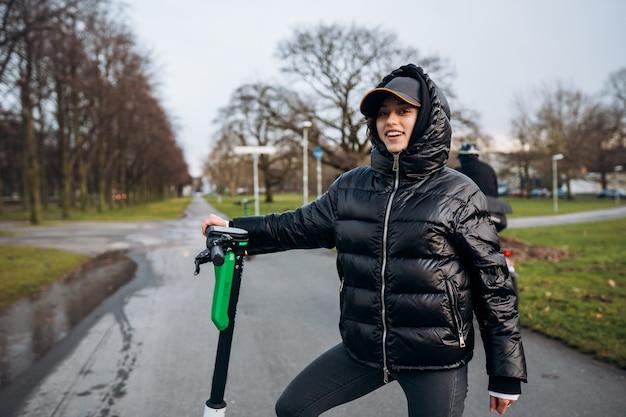 Frau in einer jacke auf einem elektroroller in einem herbstpark