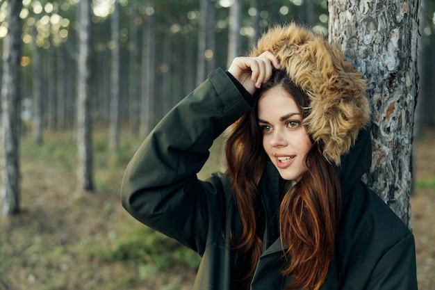 Frau in einer jacke mit einer haube nahe einem baum auf naturlebensstil im wald.