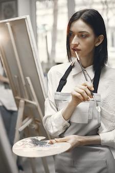 Frau in einer kunstschule, die eine schürze mit einer nachdenklichen geste trägt.
