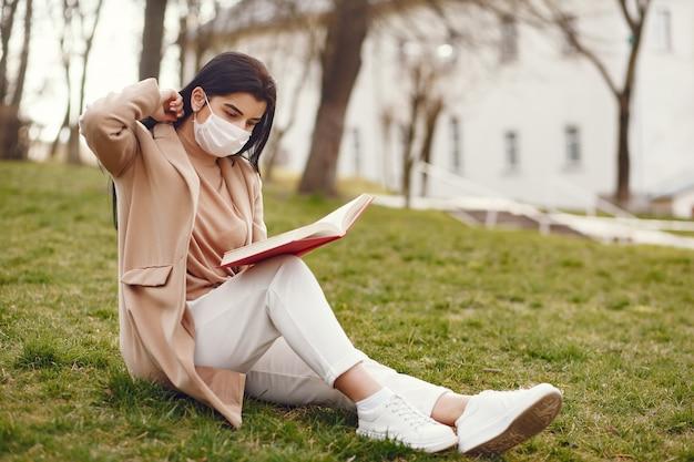 Frau in einer maske, die auf einem gras sitzt