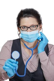 Frau in einer maske mit einem phonendoskop in ihren händen