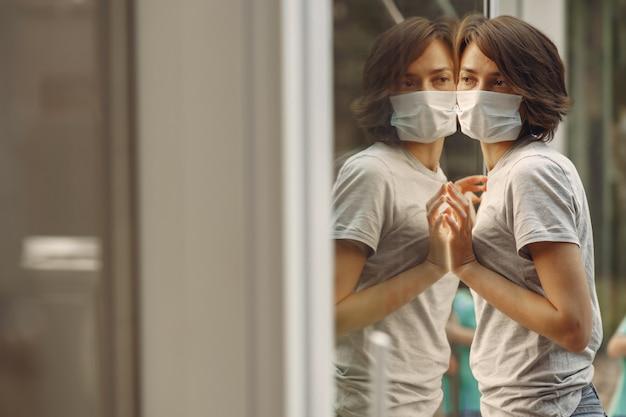 Frau in einer maske steht am fenster