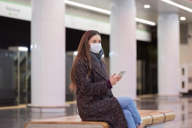 Frau in einer medizinischen gesichtsmaske sitzt in der mitte des u-bahnsteigs mit einem smartphone und wartet auf einen zug