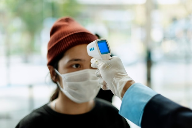 Frau in einer medizinischen maske, die ihre temperatur durch ein elektronisches thermometer gemessen bekommt