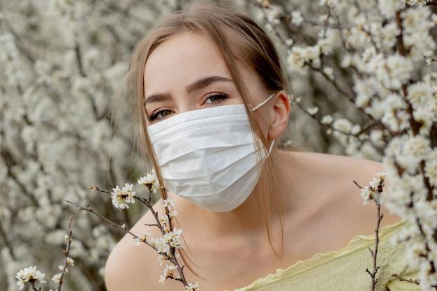 Frau in einer medizinischen maske. frau im frühling inmitten des blühenden gartens.