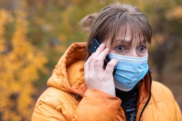 Frau in einer medizinischen maske geht in den herbstpark
