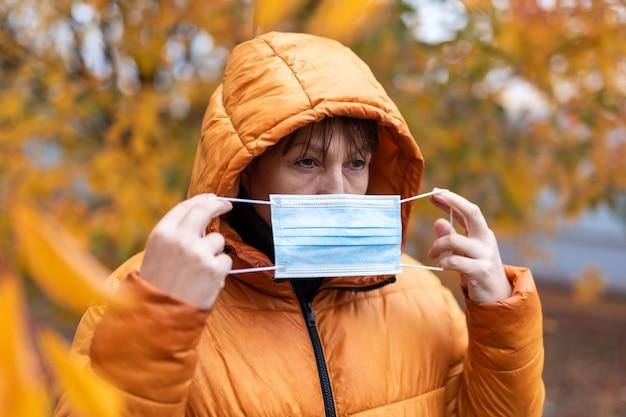 Frau in einer medizinischen maske im herbstpark