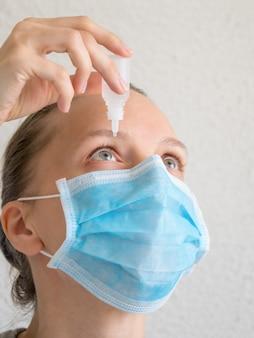 Frau in einer medizinischen maske mit augentropfen. prävention von virusinfektionen