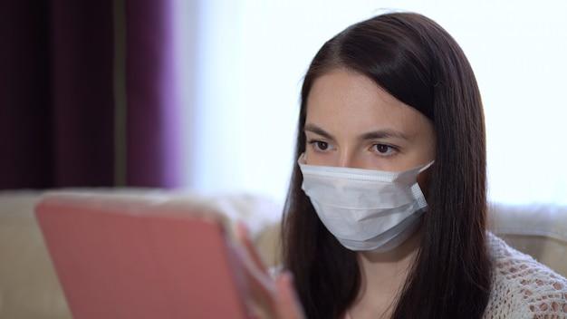 Frau in einer medizinischen maske verwendet eine tablette