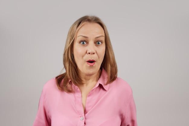 Frau in einer rosa bluse in überraschtem gefühl schaut in die kamera