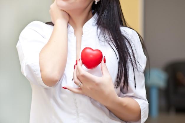 Frau in einer rosa medizinischen uniform, die ein herz in den händen hält