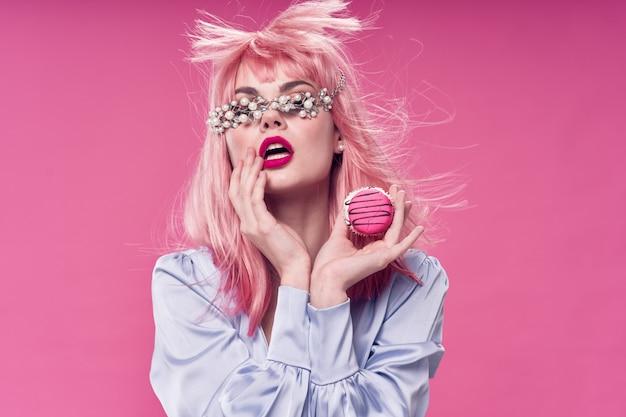 Frau in einer rosa perücke, kleidung auf einem rosa hintergrund mit essen