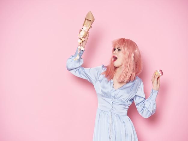Frau in einer rosa perücke, kleidung auf mit essen