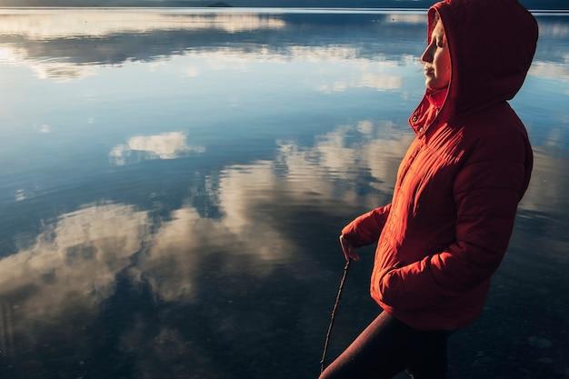 Frau in einer roten jacke mit ihren geschlossenen augen, die an einem see während eines sonnenuntergangs betrachten