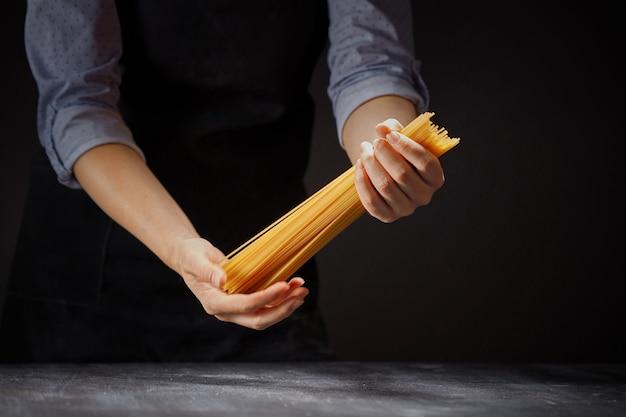 Frau in einer schürze, die einen bündel roher spaghetti hält