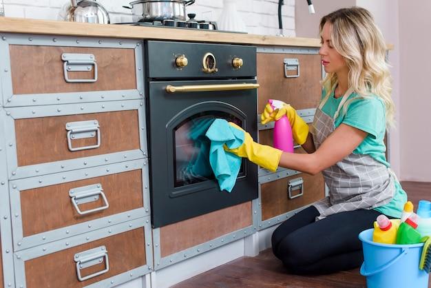 Frau in einer schürze in der küche, welche die ofentür wäscht