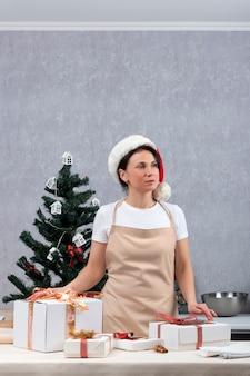 Frau in einer schürze und neujahrshut neben geschenkboxen auf neujahrsbaumhintergrund. vertikaler rahmen.