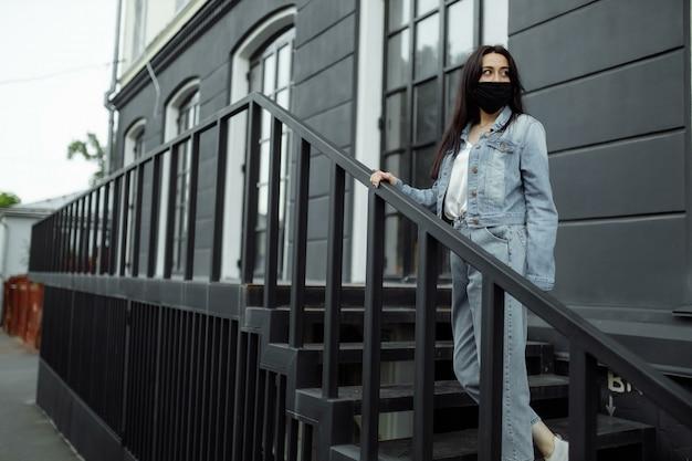 Frau in einer schutzmaske auf einem balkon schaut auf eine leere stadt