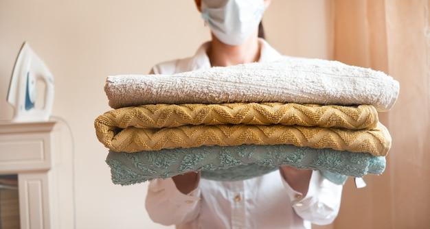 Frau in einer schutzmaske, die gefaltete handtücher in den händen hält