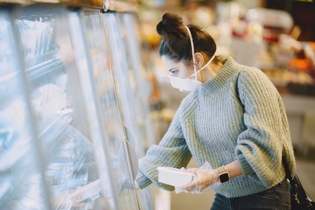 Frau in einer schutzmaske in einem supermarkt