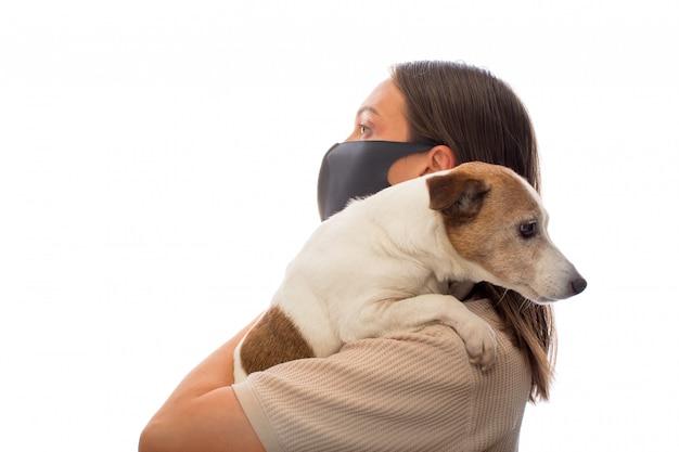 Frau in einer schutzmaske mit einem hund