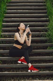Frau in einer schwarzen spoerswear, die auf einer treppe steht