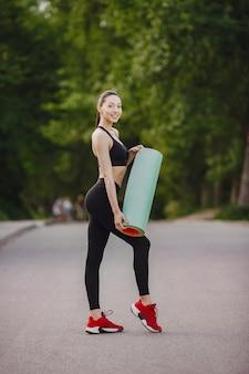 Frau in einer schwarzen sportbekleidung, die in einem wald steht