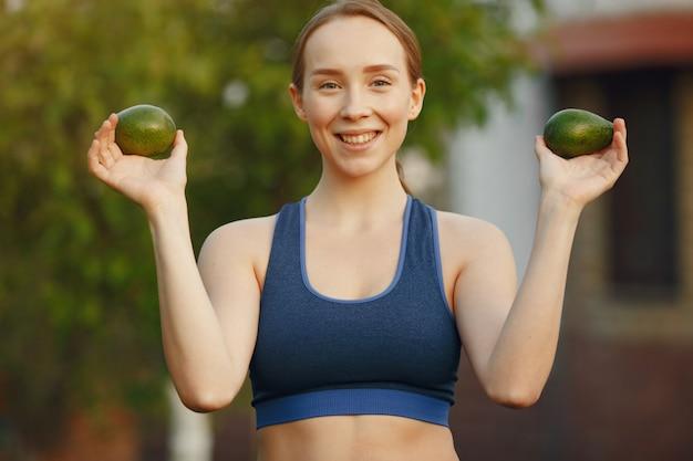 Frau in einer sportbekleidung hält früchte