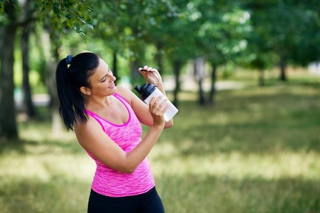 Frau in einer sportuniform hält wasser in den händen in einem park