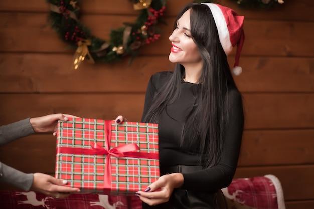 Frau in einer weihnachtsmannmütze nehmen weihnachtsgeschenkbox