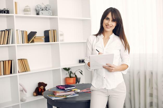 Frau in einer weißen bluse, die mit einem buch steht