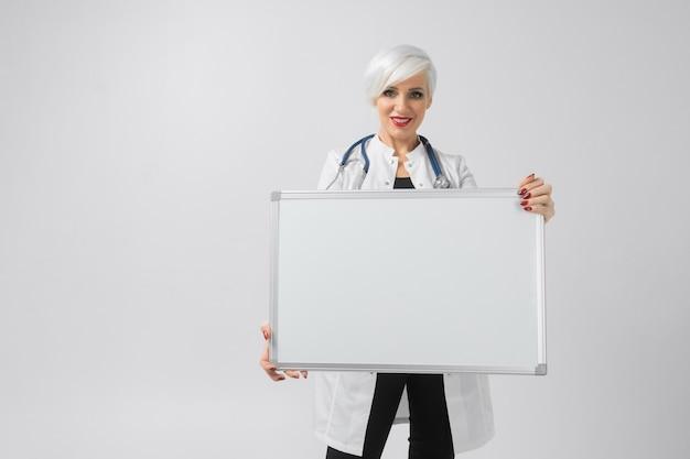Frau in einer weißen robe mit einem magnettafel in ihren händen. ein platz für ein etikett