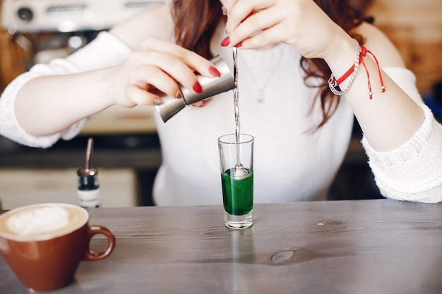 Frau in einer weißen strickjacke, die grüne spritze in glas gießt