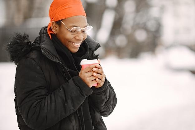 Frau in einer winterstadt. mädchen in einer schwarzen jacke. afrikanerin mit kaffee.