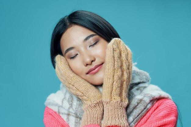 Frau in fäustlingen berührt ihr gesicht mit ihren händen und einem warmen schal rosa pullover asiatisches aussehen
