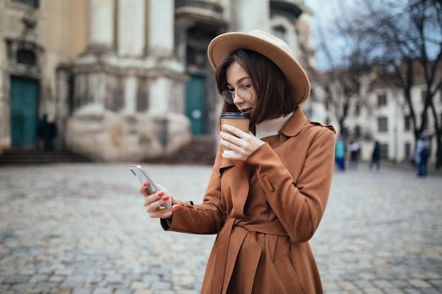 Frau in fasion hat über phote und textnachrichten auf ihrem telefon gesprochen
