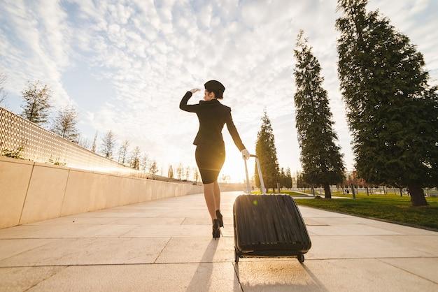 Frau in flugstewardess trägt einen großen koffer