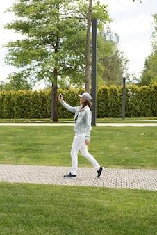 Frau in freizeitkleidung, die ein selfie auf ihrem handy macht, während sie im park spazieren geht