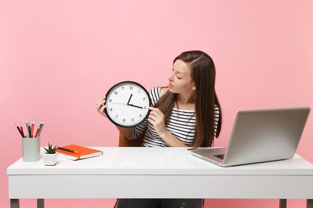 Frau in freizeitkleidung hält auf runden wecker, während sie am weißen schreibtisch mit zeitgenössischem pc-laptop einzeln auf pastellrosa hintergrund sitzt. erfolgsgeschäftskarrierekonzept. platz kopieren.