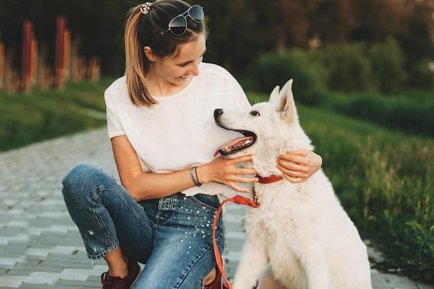 Frau in freizeitkleidung und weißer hund sitzen zusammen auf dem bürgersteig im park und umarmen sich und schauen sich an