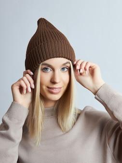 Frau in frühlingskleidung, snood-schal, hut und handschuhen. das mädchen ist blond mit blauen augen. warme kleidung für kaltes frühlingswetter