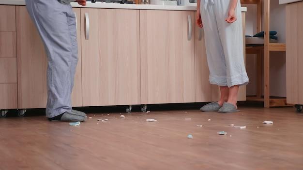 Frau in frustration, die platte bricht, während sie mit ehemann streitet. . mann und frau schreien frustriert während des gesprächs zu hause.