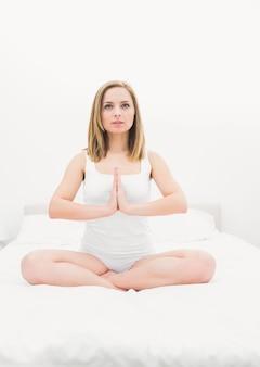 Frau in gebetsposition auf dem bett