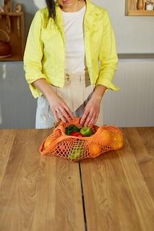 Frau in gelber jacke, die einkaufsnetz-ökotasche mit gesundem veganem gemüse und obst in der küche zu hause auspackt, vegetarisches konzept für gesunde ernährung.