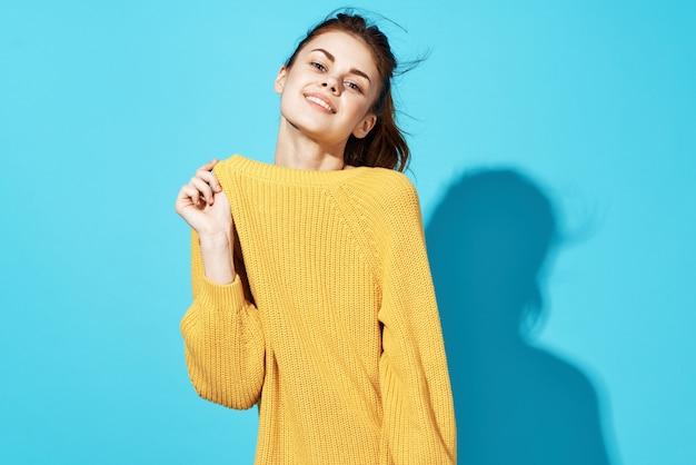 Frau in gelber pullovermode, die glamour-nahaufnahme aufwirft