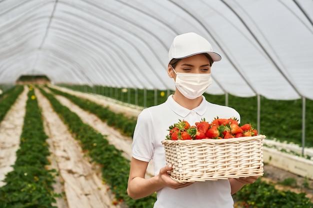Frau in gesichtsmaske, die korb mit erdbeeren trägt